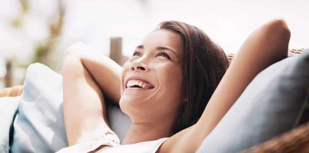 Eine Frau liegt glücklich auf dem Sofa. Sie hat die richtigen Weichen für Ihr Leben gestellt. Individuelles Personal Coaching hat ihr bei ihren Entscheidungen maßgeblich geholfen - In Frankfurt und Umgebung