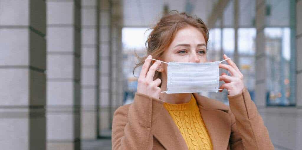 Eine Frau zieht ihre Maske an, um sich vor dem Virus zu schützen. In der Pandemie, ein ganz normaler Prozess, aber was für eine Auswirkung hat diese Pandemie auf Millionen von Jobs?
