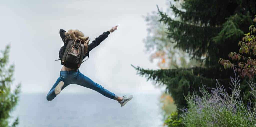 Ein Mädchen springt in die Luft. Sie hat die Ausbildung zum Coach geschafft. Jetzt ist sie ihr eigener Chef und kann andere Menschen Coachen und ihnen beim wachsen helfen